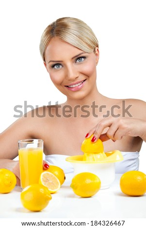 Beautiful woman squeeze on juicer and making lemonade - stock photo