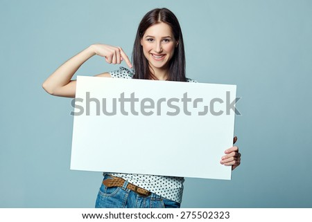 Beautiful woman standing behind, holding white blank advertising board banner, on blue background - stock photo
