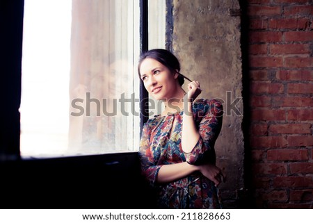 Beautiful woman standing by a window looking outside. - stock photo