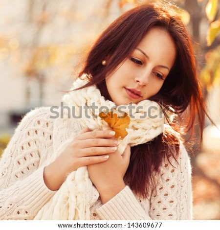 Beautiful woman standing in a park in autumn - stock photo