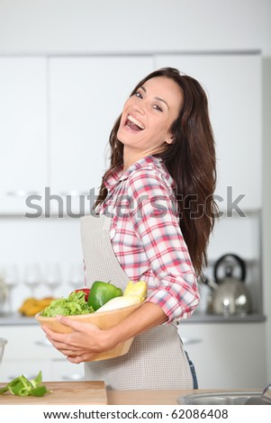Beautiful woman standing in kitchen with apron - stock photo