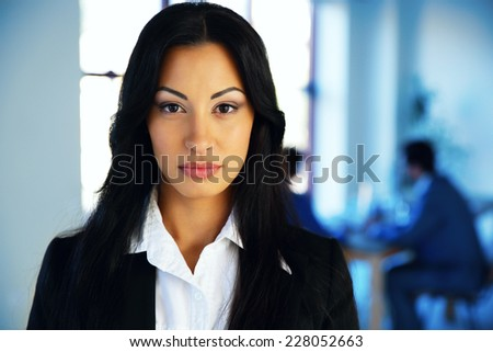 Beautiful woman standing in office with colleagues on background - stock photo
