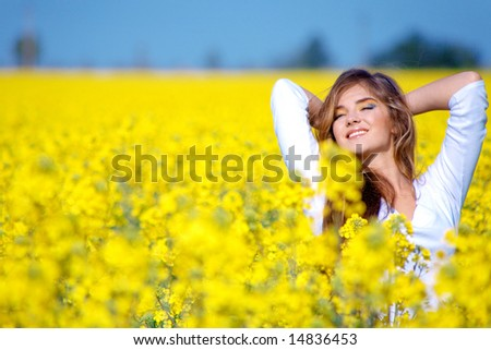 Beautiful woman standing in rapeseed field and smiling - stock photo