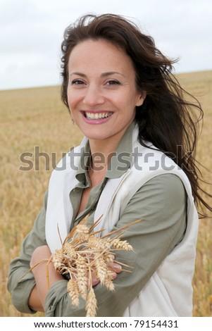 Beautiful woman standing in wheat field - stock photo