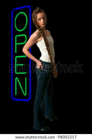 Beautiful woman standing next to a neon sign letting the world know that an establishment is open. - stock photo