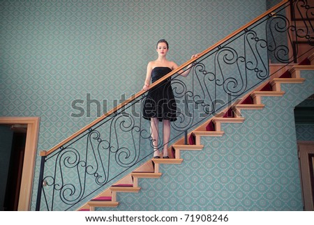 Beautiful woman standing on a staircase in a luxury hotel - stock photo