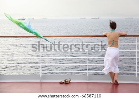 beautiful woman standing on deck of cruise ship and looking away. - stock photo