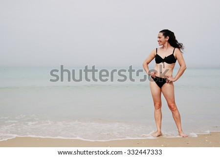 Beautiful woman standing on the beach with the sand, sea and blue sky in the background  - stock photo