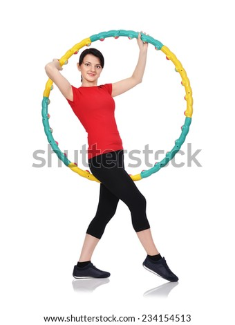 Beautiful woman standing with color hula hoop - stock photo