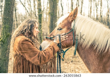 Beautiful woman stroking a brown horse - Pretty caucasian model with stallion outdoors - stock photo