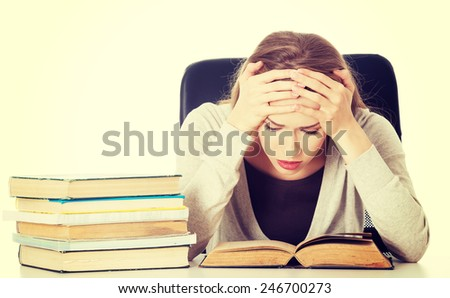 Beautiful woman student worried with stack of books. - stock photo