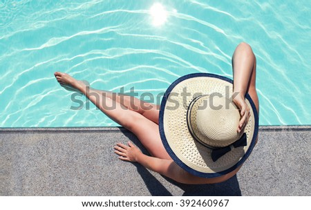Beautiful woman sunbathing by the pool top view horizontal. Summer background. Poster, mock up for design. - stock photo