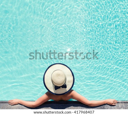 Beautiful woman sunbathing by the pool top view. Summer background. Woman sitting in swimming pool with sunhat. - stock photo