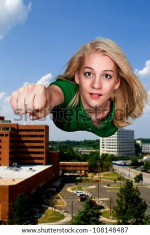 Beautiful woman super hero flying through the sky - stock photo