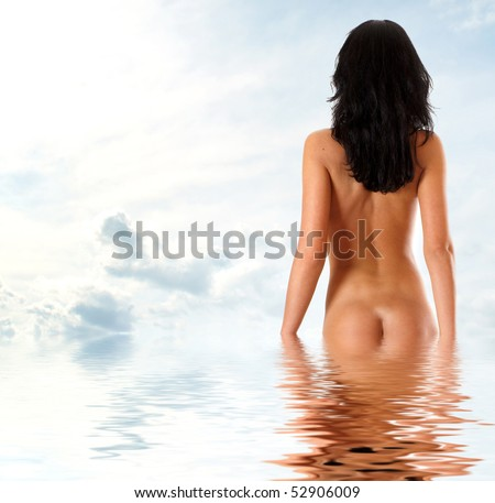 Beautiful woman taking off jeans over resort background - stock photo