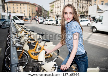 Beautiful woman taking rent bicycle in the city - stock photo