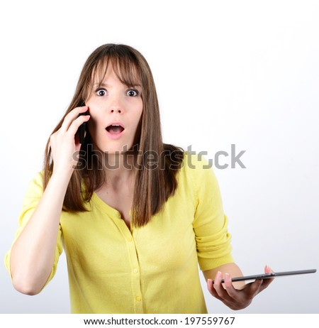 Beautiful woman talking on cellphone and being in shock of news she hears against white background - stock photo