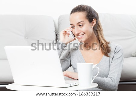 Beautiful woman talking on the telephone and working at home - stock photo