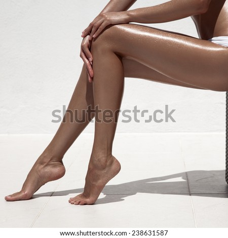 Beautiful woman tan legs. Against white wall. - stock photo