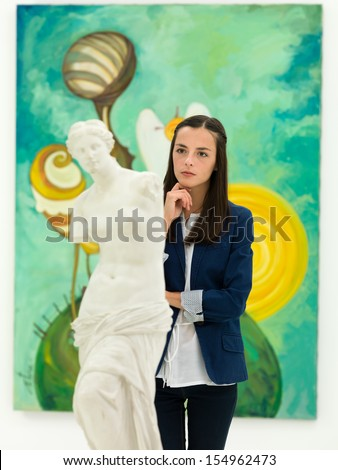 beautiful woman thoughtfully looking at artworks in museum - stock photo