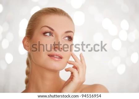 Beautiful woman touching her face. - stock photo