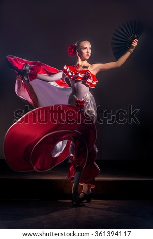 Beautiful Woman traditional Spanish Flamenco dancer dancing in a red dress with black fan - stock photo