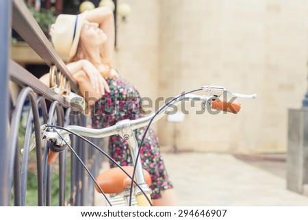 beautiful woman travel at europe by city vintage bicycle at summer time, she is dressed in elegant dress and standing on bridge at background. Selective Focus at bicycle handle at foreground - stock photo