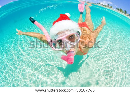 beautiful woman underwater with snorkel and christmas hat - stock photo