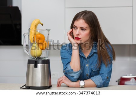 Beautiful woman using blender at her kitchen - stock photo