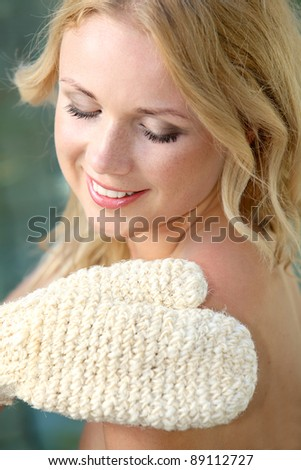 Beautiful woman using exfoliating glove - stock photo