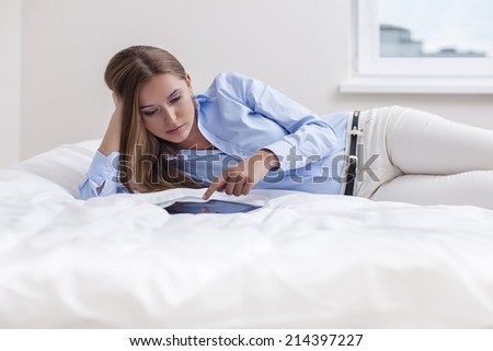 Beautiful woman using tablet computer on her bed - stock photo