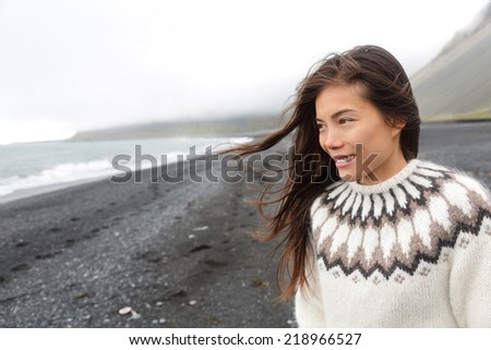 Beautiful woman walking on black sand beach on Iceland wearing Icelandic sweater. Pretty multiracial female model looking pensive at ocean sea smiling happy. - stock photo