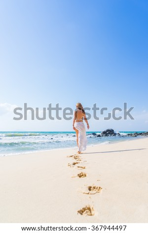 Beautiful woman walking on the white sandy beach with her footprints back - stock photo