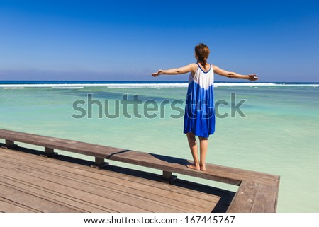 Beautiful woman walking with arms open on a beautiful tropical beach - stock photo