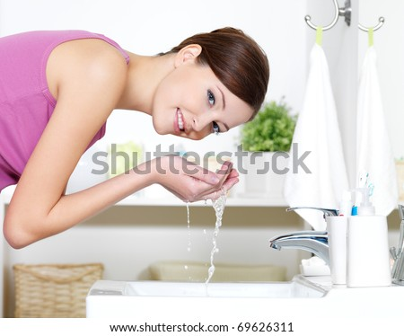 Beautiful woman washing her face by clean water standing in bathroom - stock photo