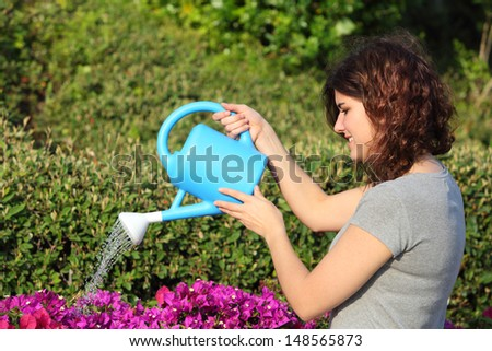 Beautiful woman watering flowers with a watering can in the garden - stock photo