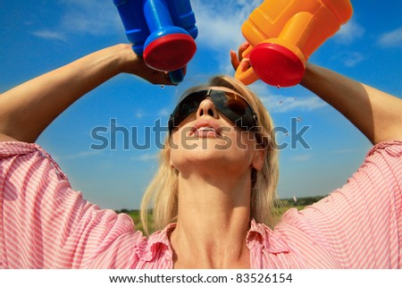 Beautiful  woman watering herself at hot summer day - stock photo