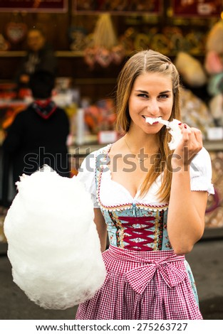 Beautiful woman wearing a traditional Dirndl dress with cotton candy floss at the Oktoberfest - stock photo