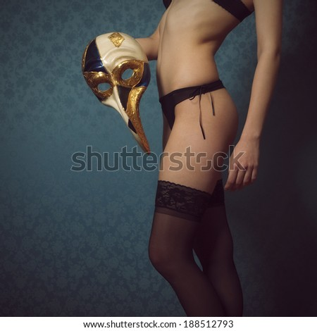 Beautiful woman, wearing black underwear an playing with a venetian mask - stock photo