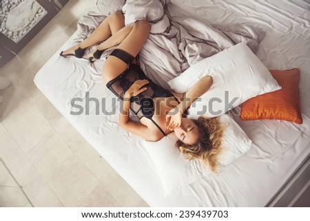 beautiful woman wearing black underwear yawning in her bed (top view) - stock photo
