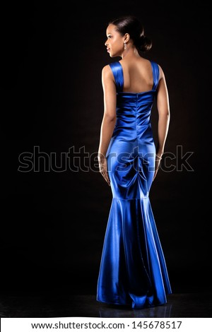 beautiful woman wearing blue evening dress on black background - stock photo