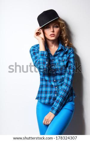 beautiful woman wearing cap standing near white wall - stock photo