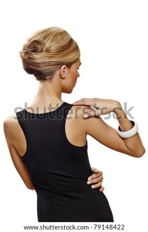 beautiful woman wearing hair in french roll updo in sexy black dress standing with her back against white background . - stock photo