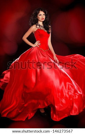 Beautiful woman wearing in magnificent red dress isolated on black background. Studio photo. Fashion. - stock photo