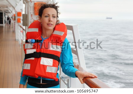 Beautiful woman wearing in orange life jacket looks into distance at deck of ship - stock photo
