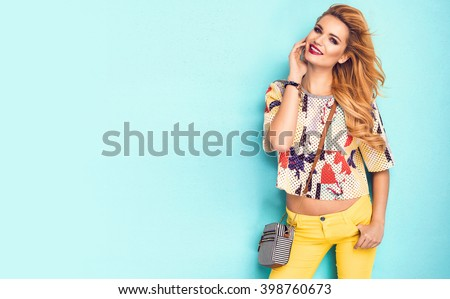 Beautiful woman wearing nice clothes, handbag posing on turquoise background. Fashion spring photo. Bright colors - stock photo
