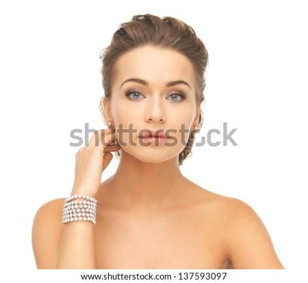 beautiful woman wearing pearl earrings and bracelet - stock photo