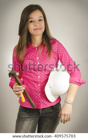 Beautiful woman, wearing pink shirt, holding a hammer, a pliers, and with a hard hat under her arm, in a white background. - stock photo
