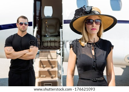 Beautiful woman wearing sunhat with bodyguard and private jet in background - stock photo