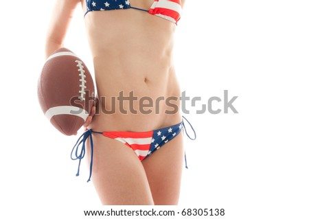 Beautiful woman wearing the United States flag bikini holding a football isolated over white background - stock photo